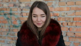 Portret van een leuk meisje op de bakstenen muurachtergrond Volledige Video HD stock footage
