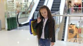 Portret van een leuk meisje in een winkelcentrum met pakketten dichtbij roltrap stock video