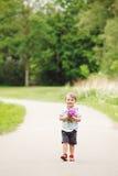Portret van een leuke aanbiddelijke grappige kleine glimlachende jongenspeuter die in park met lilac purpere roze bloemen in hand Stock Foto's