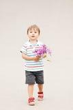 Portret van een leuke aanbiddelijke grappige kleine glimlachende jongenspeuter die in park met lilac purpere roze bloemen in hand Royalty-vrije Stock Afbeeldingen