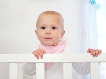 Portret van een leuke baby die zich in witte wieg bevinden Royalty-vrije Stock Afbeelding