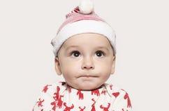 Portret van een leuke babyjongen die omhoog denkend het dragen van een Kerstmanhoed kijken Stock Afbeelding