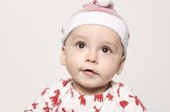 Portret van een leuke babyjongen die omhoog denkend het dragen van een Kerstmanhoed kijken Royalty-vrije Stock Afbeeldingen