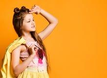 Portret van een leuke, charmante, aantrekkelijke, vrolijke tiener, kijkend aan de kant op een gele achtergrond en houdend een jas stock foto