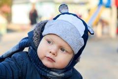 Portret van een leuke kleine blauw-eyed jongen met een geinteresseerde blik in een hoed, een sjaal en een jasje in de vroege lent stock afbeelding