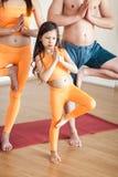 Portret van een leuke kleine het glimlachen meisje het praktizeren yoga, in een oranje kostuum, die yoga doen Het maken van Namas Stock Afbeeldingen