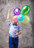 Portret van een leuke kleine jongen in jeans, blauwe overhemd en vlinderdas w Stock Afbeeldingen