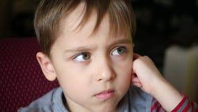Portret van een leuke kleine jongen met een nadenkende blik De beeldverhalen van kindhorloges stock footage