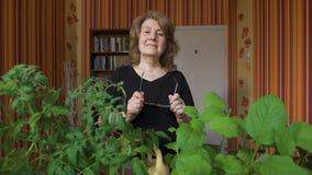 Portret van een leuke oude vrouw thuis Het kost over zijn zaailingen, het glimlachen Haar hobby stock videobeelden