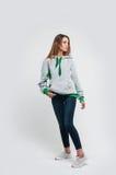Portret van een leuke positieve blondevrouw in een hoodie op grijze bac Stock Fotografie