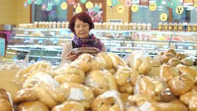 Portret van een leuke teruggetrokken vrouw in een kruidenierswinkelopslag in de broodafdeling stock video