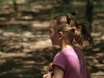 Portret van een lopend meisje in een roze T-shirt en met twee staarten op haar hoofdâ stock foto
