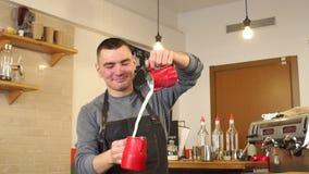 Portret van een mannelijke Barista in een koffiewinkel, giet hij melk van Kop aan Kop stock footage