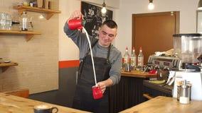 Portret van een mannelijke barista in een koffiewinkel, giet hij melk van kop aan kop stock video
