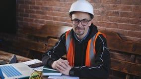 Portret van een mannelijke ingenieur achter een Bureau bij een helm en een beschermende vestmens die camera en het glimlachen bek stock footage