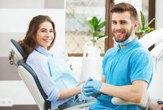 Portret van een mannelijke tandarts en een jonge gelukkige vrouwelijke patiënt stock foto