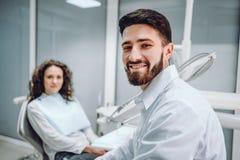 Portret van een mannelijke tandarts en een jonge vrouw in een tandartsbureau royalty-vrije stock fotografie