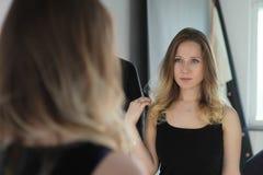 Portret van een meisje dat haar haar doet stock afbeeldingen