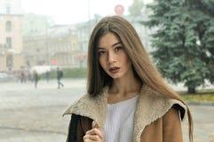 Portret van een meisje dat rond het vierkant in een mistige stad loopt stock afbeelding