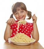 Portret van een meisje dat spaghetti eet stock foto's