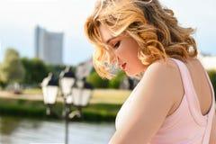 Portret van een meisje in een elegant kostuum tegen een achtergrond van water in het zonlicht in de stad royalty-vrije stock fotografie