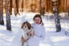 Portret van een meisje met een hond in het hout in de winter stock fotografie