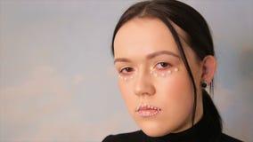 Portret van een meisje met make-up Het gezicht van een model met ballen wordt verfraaid die stock video