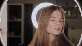 Portret van een meisje met een weerspiegeling van het ringvormige LEIDENE licht in de ogen stock video