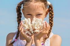 Portret van een meisje met witte koralen in handen Stock Fotografie