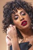 Portret van een meisje met zwart krullend haar met make-up in een avondjurk die oorringen dicht omhoog dragen stock foto