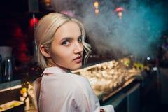 Portret van een meisje in een nachtbar, achter de teller stock foto's