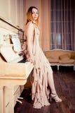 Portret van een meisje over de piano Stock Afbeeldingen