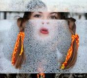 Portret van een meisje voor een ijzig venster Stock Afbeeldingen