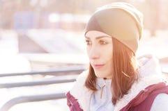 Portret van een meisjesatleet in een hoed met handschoenen en een warm vest naast een trainingspeelplaats in openlucht in de wint stock foto's