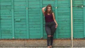 Portret van een meisjesmodel plus grootte op de achtergrond van een groene muur stock footage