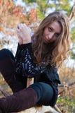 Portret van een meisjeszitting op een logboek Stock Fotografie