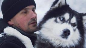 Portret van een mens in de winterbovenkleding die en aan schor in openlucht koesteren spreken Kerel met zijn huisdier stock videobeelden