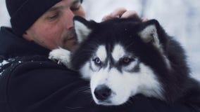 Portret van een mens in de winterbovenkleding die en schor in openlucht koesteren strijken Kerel met zijn huisdier stock footage