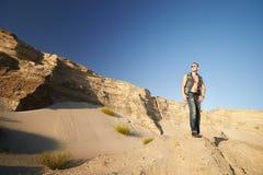 Portret van een mens in denimkleren op het zand stock fotografie