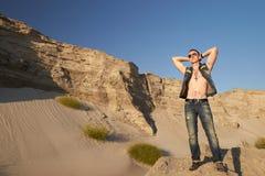 Portret van een mens in denimkleren op het zand stock foto
