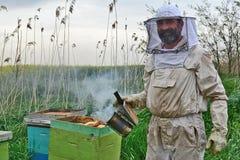 Portret van een mens in het bijenkostuum, naast de bijenkorf stock foto's