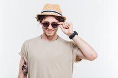 Portret van een mens in hoed die zijn oogglazen opstijgen Stock Afbeeldingen