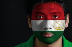 Portret van een mens met de vlag van Tadzjikistan op zijn gezicht op zwarte achtergrond wordt geschilderd die royalty-vrije stock foto's