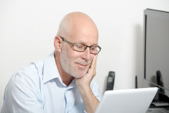 Portret van een mens op middelbare leeftijd met een digitale tablet stock afbeelding