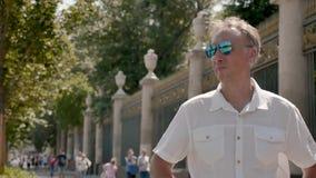Portret van een mens op middelbare leeftijd in een wit overhemd en zonnebril, met een zwarte klok stock footage
