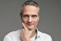 Portret van een mens in een overhemd op een grijze achtergrond stock foto