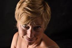 Portret van een midden oude vrouw op zwarte royalty-vrije stock foto