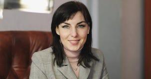 Portret van een midden oude vrouwelijke zitting als leervoorzitter in een licht bureau stock video