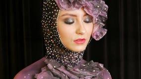 Portret van een modieus hoog model van het maniermeisje met expressieve make-up rokerige ogen die in de studio op een fluweelzwar stock video