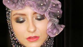 Portret van een modieus hoog model van het maniermeisje met expressieve make-up rokerige ogen die in de studio op een fluweelzwar stock footage